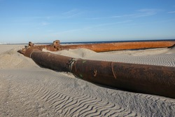 A thick rusty pipeline making a right angle turn on a sandy beach near the ocean at a beach replenishment site