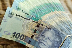 A thick stack of one hundred Rand notes cash South African ZAR tied together with an elastic band on a textured table