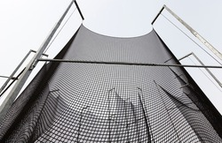 a thick strong net that restricts sports equipment and creates safety for spectators and other people, a black net on the territory of a hammer throwing sports ground