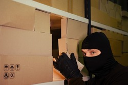 A thief in a black mask steals a box of goods in a warehouse in the dark. Concept of problems with theft of goods and postal parcels