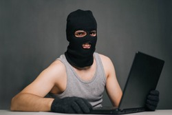 A thief in a black mask stole a laptop. A man in a balaclava and a computer in hand on a gray background. The hacker is hacking the computer. Steals information. A young man breaks the law.