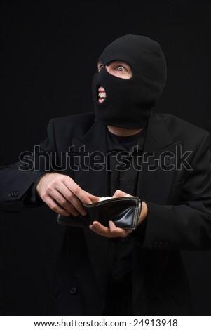 A thief wearing a balaclava snooping through a wallet, shot against a dark background