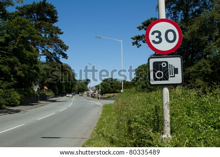 A thirty mile an hour sign and a speed camera sign on a post next to a road with cars in the distance. #80335489