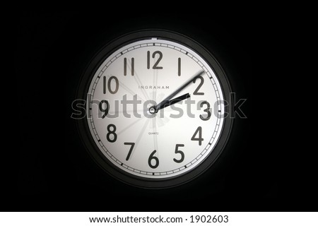 A thirty second exposure of a simple black clock showing the second hand every five seconds.