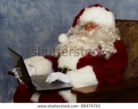 A thoroughly modern Santa claus checks his list on his laptop computer