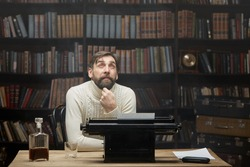 A thoughtful concerned male writer working on a novel on a typewriter, looking up, thinks about solving a problem in the home office, a serious man is looking for inspiration, feels a lack of ideas.