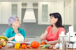 A thoughtful daughter or hired actress from a rental family service regularly visits her old mother or client to cook a vegetable dish together. It is very important to pay attention to the elderly.