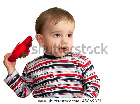 A thoughtful kid in striped shirt is holding red heart; isolated on the white background