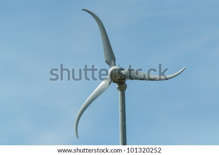 A three-bladed wind turbine spins in the wind.