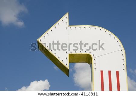 A three-dimensional metal arrow sign.