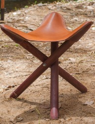 A three-legged chair made of wood and leather.Brown chair made by human hand.