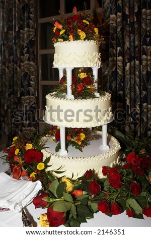 a three tiered yellow wedding cake with roses