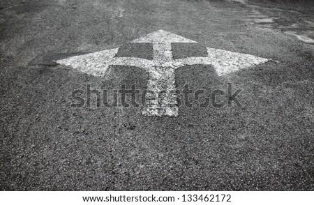 A three way arrow symbol on a black asphalt road surface.