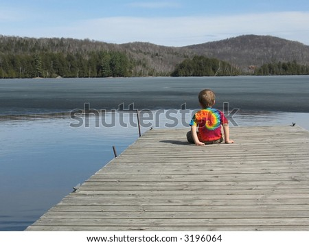 A three year old boy in a tie-dyed t-shirt faces a half-frozen lake from a gray dock in spring near Mont-Tremblant, Quebec.