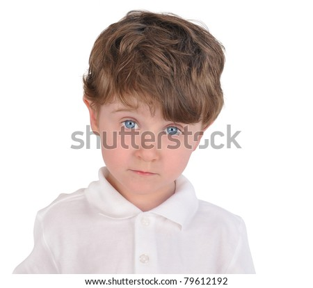 A three year old boy is isolated on a white background and looks sad and curious. He has a white shirt on.