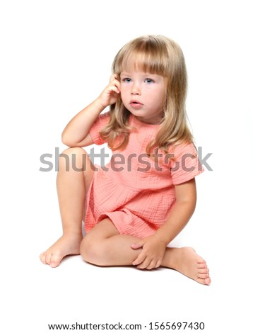 A three-year-old Caucasian girl. Girl in a dress. A girl with blue eyes and long hair. Isolated on white background.
