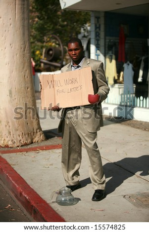 """a thursty business man stands on a city street with a cardboard sign that reads """"will work for Lattes"""" - stock photo"""