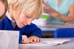 A tight closeup of a school boy in a classroom under selective focus intently reading a textbook while pointing and sliding his finger over each word