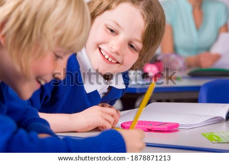 A tight closeup of two cute smiling children in a classroom under selective focus wearing school uniform solving their math problems having their teacher sitting in the background Stock photo ©