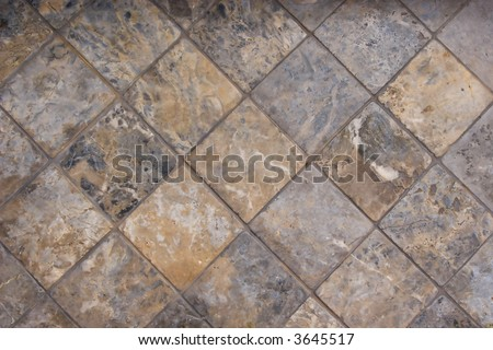 A tile floor made of complimentary earthtone shades of marble.