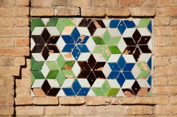 A Tile mosaic with the David Star in three different colors, blue, green, and brown, in a brick wall. Toledo, Spain