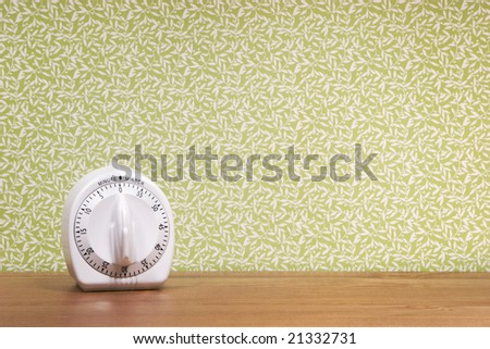 A timer sits on a wood surface against a patterned green background.