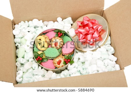A tin of colorful Christmas cookies packed in peanuts and ready for mailing.  White background.