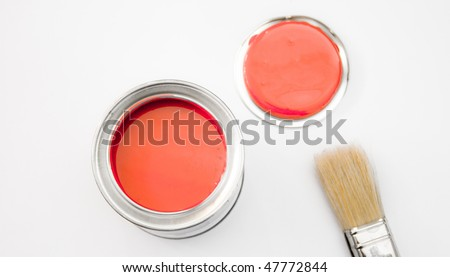 A tin of red paint with a brush and a lid