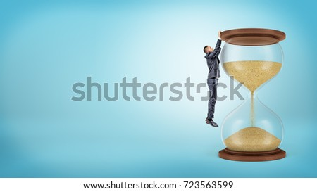 A tiny businessman hangs on his hangs from a large hourglasses wooden edge. Keeping in time. Never be late. Time for new business. #723563599