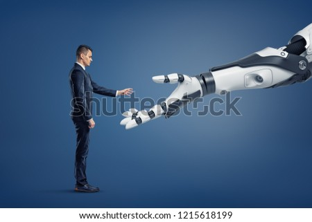 A tiny businessman stands in a side view and lifts his hand to touch a giant robotic arm. Getting to know new things. Current technologies in business. Greet modern inventions.