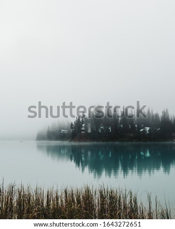 A tiny kayak and water reflections of the peninsula of Emerald Lake surrounded by towering pine trees and thick eerie fog in Yoho National Park, BC, Canada. stock photo