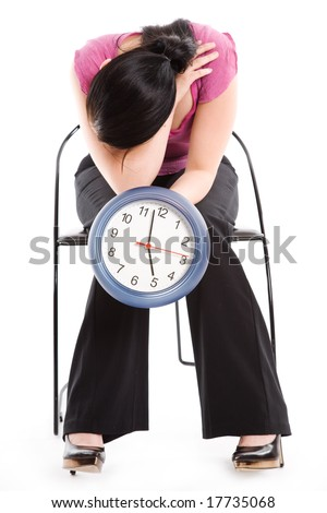 A tired businesswoman holding a clock waiting for 5pm to come can be used as a time concept