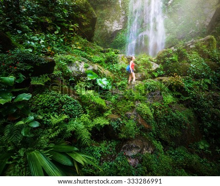 A tired but happy tourist woman looking at the waterfall in the Central America jungles Ecotourism concept image travel stock photo