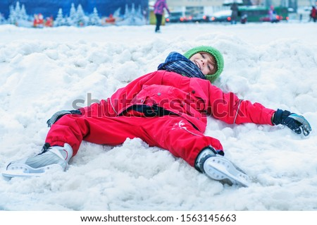 A tired child lies in the snow near the skating rink with his legs spread on the sides. Winter outdoor activities and outdoor sports. Fatigue from ice skating. Have fun until you drop #1563145663