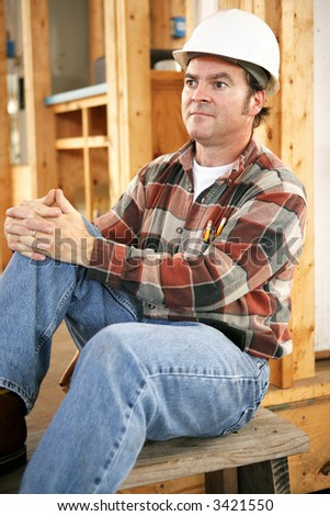 A tired construction worker sitting down resting at the end of the day.  Authentic construction worker on actual job site. - stock photo