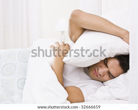A tired looking man in bed.  He is holding a pillow over his head and is scowling. Horizontally framed shot.