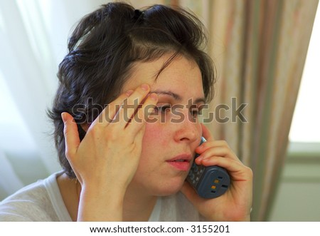 A tired young woman receives bad news on the phone...