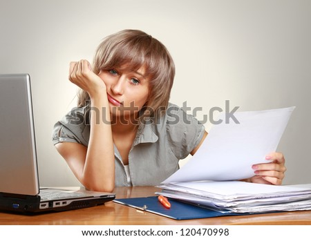 A tired young woman sitting at the desk, having a lot of paperwork to do, isolated on grey