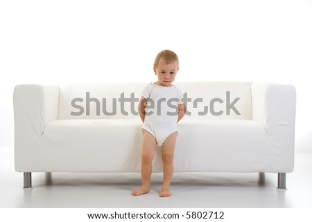 A toddler/child stands in front of a clean, white sofa, putting his hands behind his back.