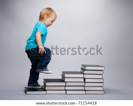 A toddler climbing on a steps made of books