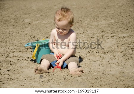 A toddler digs in the sand at the beach