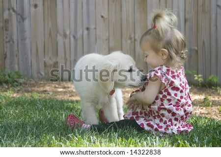 A toddler girl laughing with a golden retriever puppy