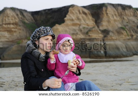 A toddler girl with her mother enjoys yogurt and energy bar on the beach just after sunset. Lit by natural available light only - no flash.