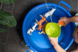 a toddler is playing with animal toys while taking a bath with a blue bucket of water