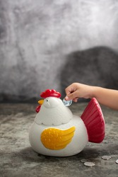 a toddler is putting a coin into a piggy bank in the shape of a chicken