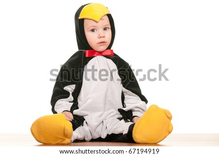 A toddler is sitting in a carnival suit of a penguin; isolated on the white background
