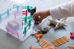 a toddler playing animal toys. selective focus.
