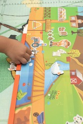 a toddler playing magnetic toy animal farm