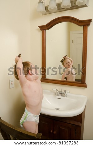 A toddler stands on a chair in front of a bathroom mirror and tries to brush his own hair