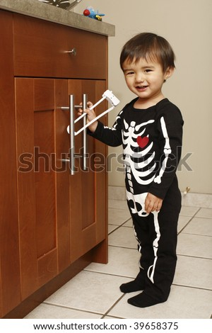 A toddler wearing a Halloween costume in the kitchen and playing with a child-proof lock.